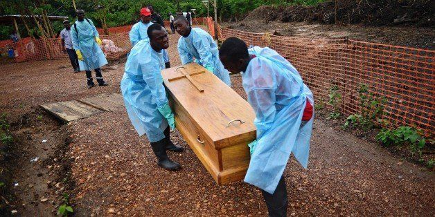Sierra Leonese government burial team members wearing protective clothing carry the coffin of an Ebola victim on August 14, 2