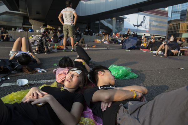 HONG KONG - SEPTEMBER 30: Protesters sleep on the streets outside the Hong Kong Government Complex just after sunrise on Sept