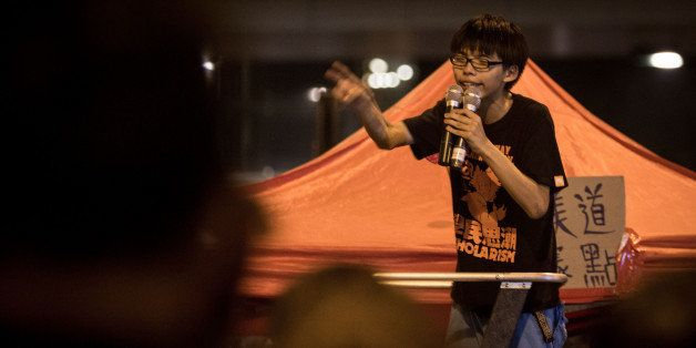 HONG KONG - OCTOBER 01:  17 year-old student protest leader Joshua Wong speaks to fellow students on the street outside the H
