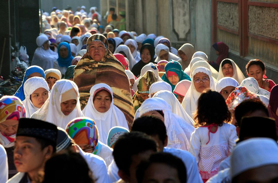 In this photo taken on Sunday, Oct. 5, 2014, Muslims perform a morning prayer marking the Eid al-Adha holiday on a street in