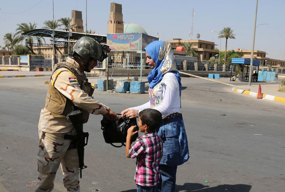 An Iraqi Army soldier searches a woman's bag amid tight security during Eid al-Adha celebrations in Baghdad, Iraq, Monday, Oc