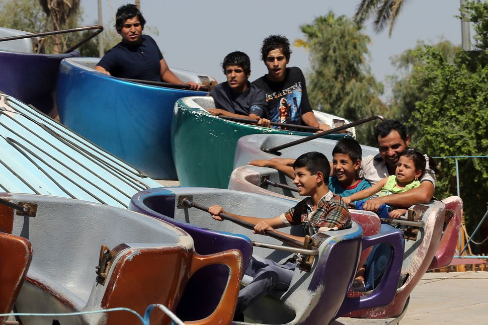 Iraqis take a ride at an amusement park during Eid al-Adha celebrations in Baghdad, Iraq, Monday, Oct. 6, 2014.