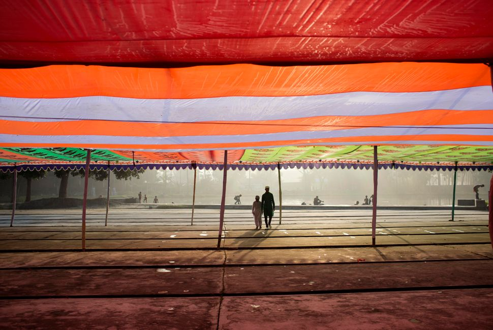 Bangladeshi Muslims under a makeshift tent as they arrive to attend morning prayers for Eid al-Adha in Mymensingh, on the out