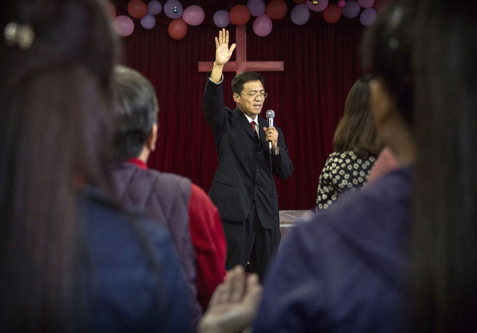 A Chinese Christian pastor leads prayers during a service at an underground independent Protestant Church on October 12, 2014