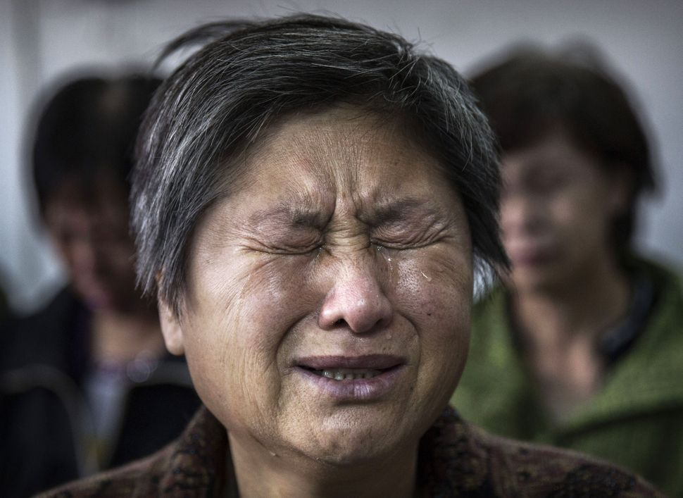 A Chinese Christian woman weeps during a ceremony at an underground independent Protestant Church on October 12, 2014 in Beij