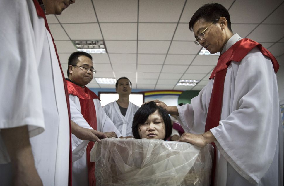 A new Chinese Christian woman sits in a small tub of water as a Pastor prays as she is baptized during a ceremony at an under