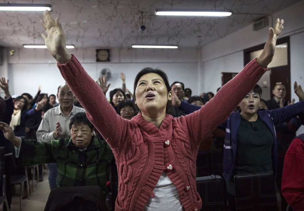 A Chinese Christian woman sings during a prayer service at an underground independent Protestant Church on October 12, 2014 i