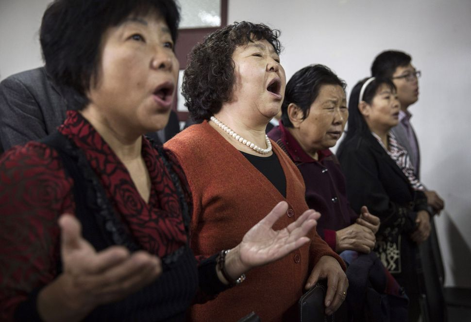 Chinese Christians sing during a prayer service at an underground independent Protestant Church on October 12, 2014 in Beijin