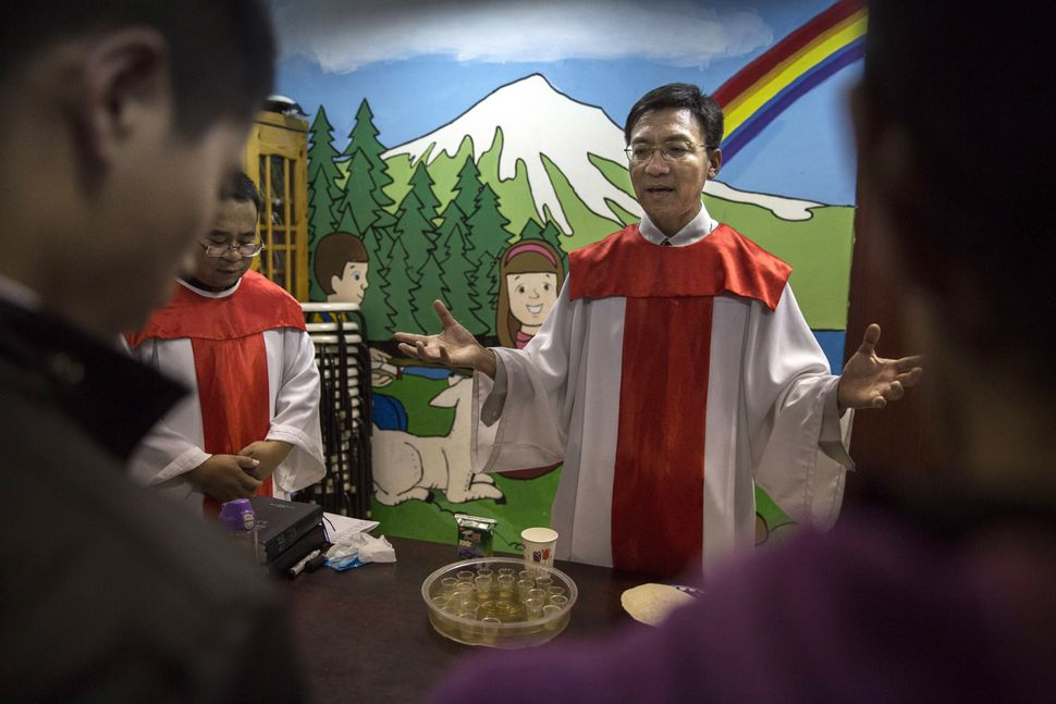 A Chinese pastor prays with newly baptized Christians during a ceremony at an underground independent Protestant Church on Oc