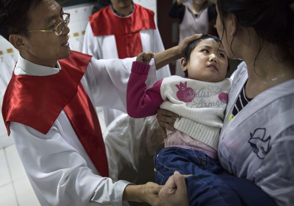 A pastor baptizes a new Chinese Christian woman and her young daughter during a ceremony at an underground independent Protes