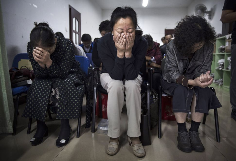 Chinese Christians pray during a service at an underground independent Protestant Church on October 12, 2014 in Beijing, Chin