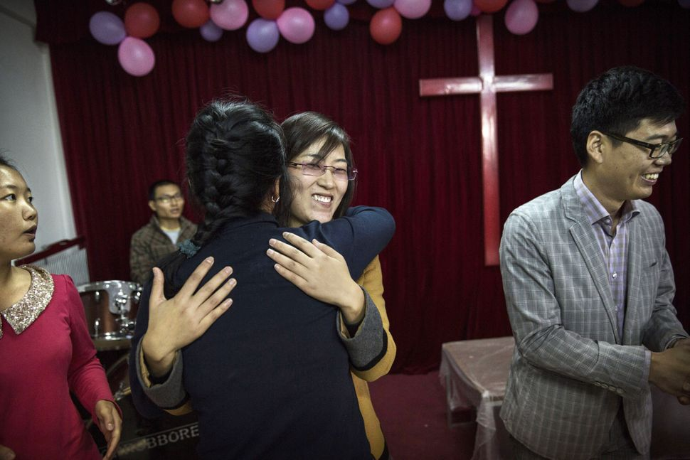 A Chinese Christian woman is embraced by another member of the congregation as she is acknowledged for attending for the firs