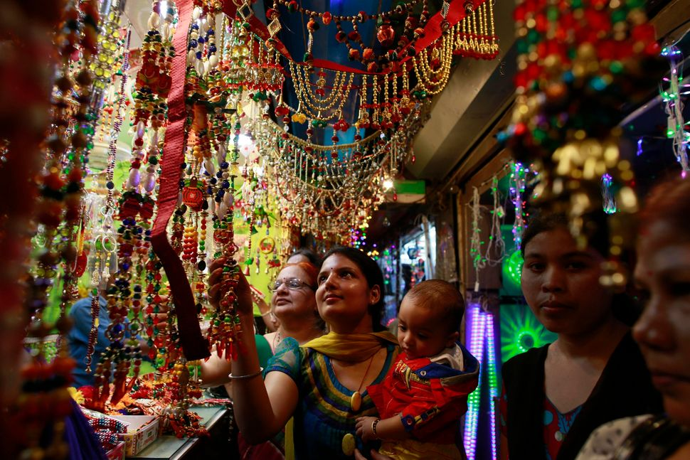 An Indian woman carrying an infant looks at decorative items as she shops ahead of Diwali, in Gauhati, India, Tuesday, Oct. 2