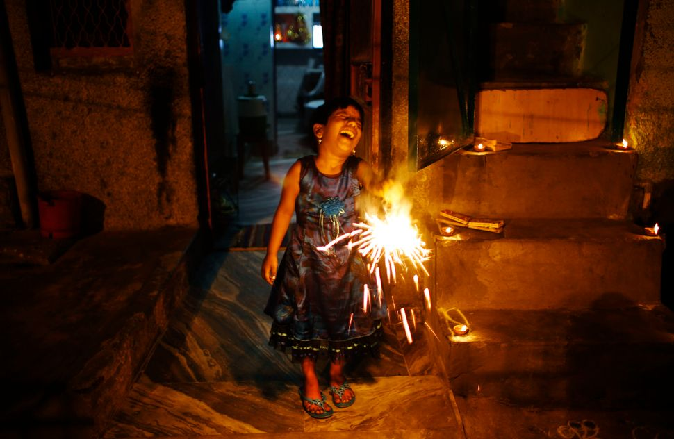 A young Indian girl laughs as she plays with a firecracker during Diwali in New Delhi, India, Thursday, Oct. 23, 2014.