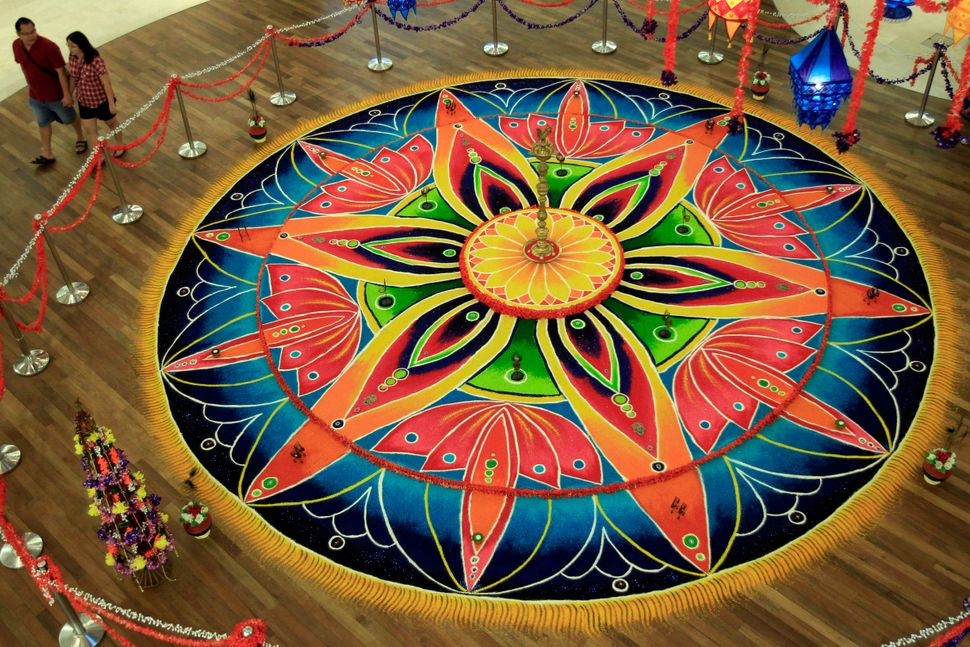 "Shoppers in a mall in Kuala Lumpur, Malaysia, walk past a piece of Indian traditional artwork known as ""Kolam,"" a form of san"