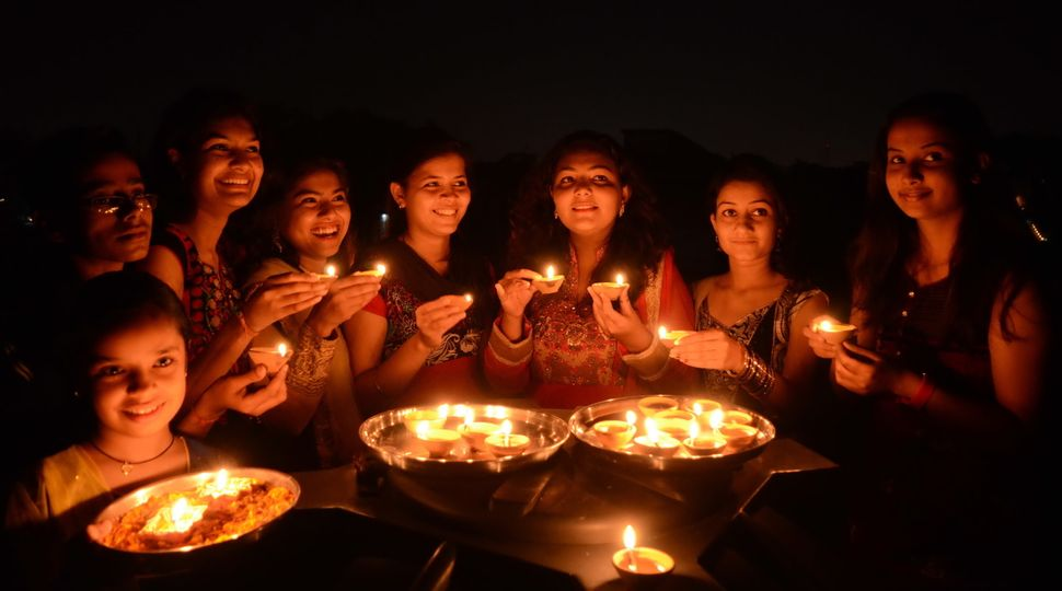Girls light earthen lamps on the eve of Diwali on Oct. 22, 2014 in Bhopal, India.