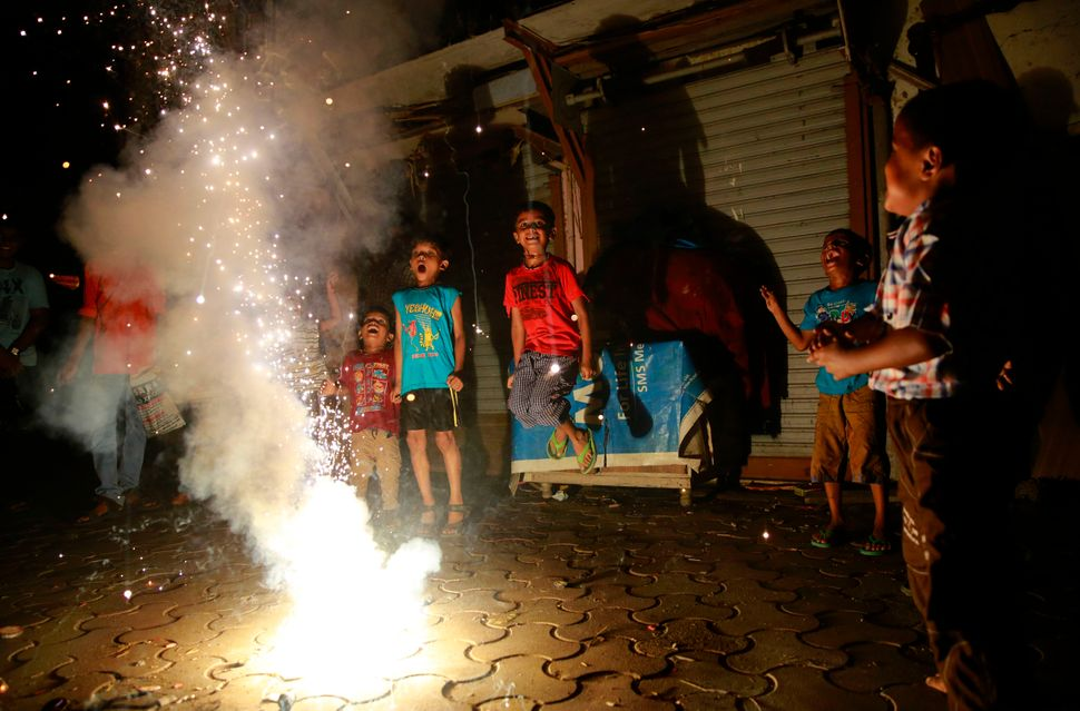 A child living in a shanty area jumps as he watches a firecracker light up during Diwali celebrations in Mumbai, India, Thurs