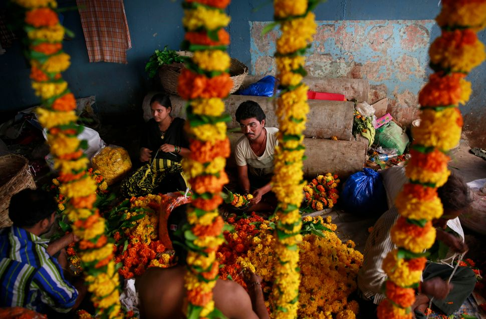 Roadside vendors prepare garlands of marigold in the early morning of Diwali at a market in Mumbai, India, Thursday, Oct. 23,