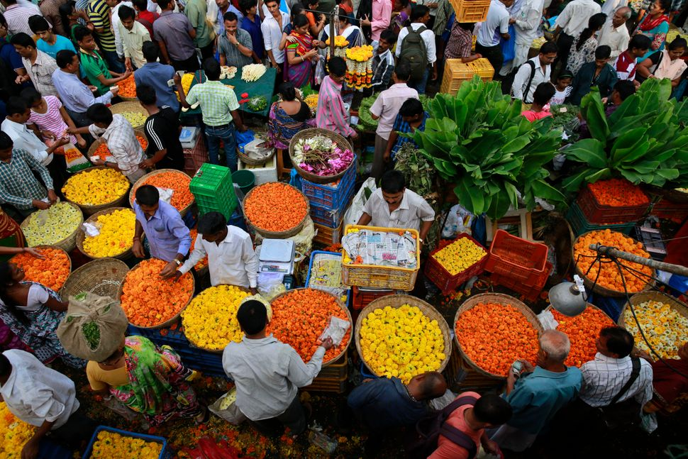 People in Mumbai, India, throng a market selling marigold flowers in the early morning of Diwali, Thursday, Oct. 23, 2014.