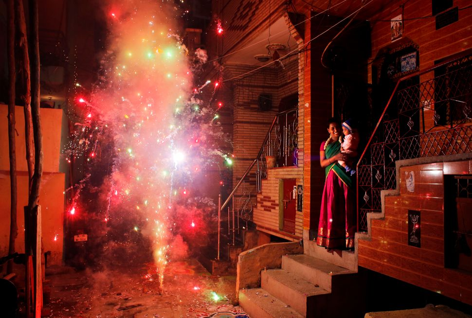 An Indian woman holds her child and watches a firecracker light up during Diwali in New Delhi, India, Thursday, Oct. 23, 2014
