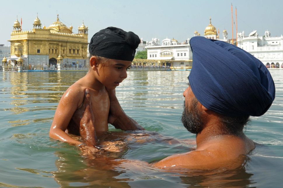 An Indian Sikh devotee holds a child as they take a dip in the holy sarover (water tank) during Diwali at the Golden Temple i