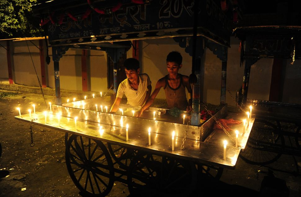 An Indian streetfood vendor lights candles around the edge of his cart to celebrate Diwali in Allahabad, India, on October 23