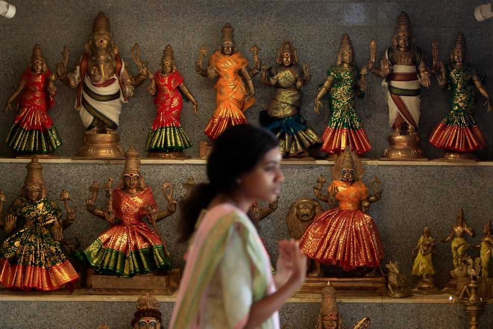 A Hindu devotee walks past statues of gods during Diwali at Sri Maha Mariamman Temple in Klang, outside Kuala Lumpur, Malaysi