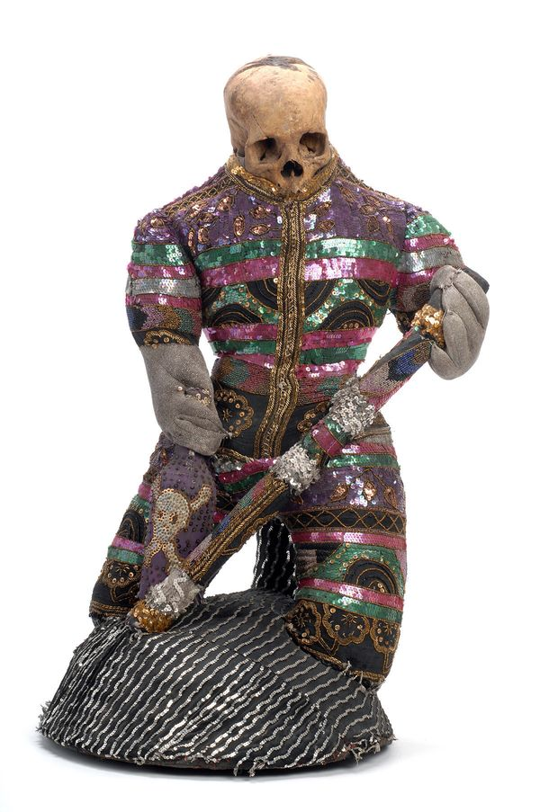 This sequin-covered figure with a human skull portrays a forest spirit named Zazi Maza Wangòl, a protector of individuals and