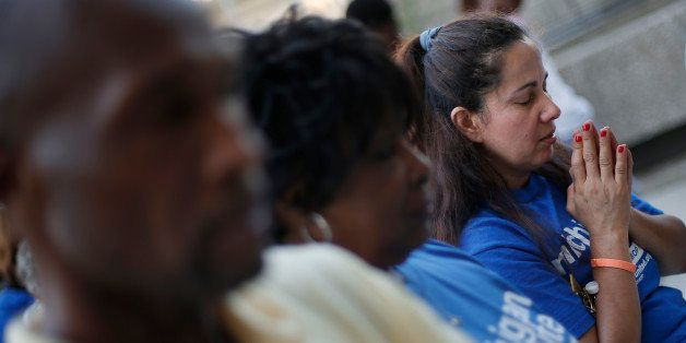 Mayra Valle prays at a prayer vigil for Michael Brown outside the McNamara Federal Building in Detroit Monday, Aug. 25, 2014.