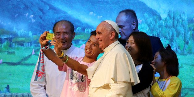 Pope Francis poses for a selfie with young people during a meeting with Asian youth at the Solmoe Sanctuary in Dangjin, South