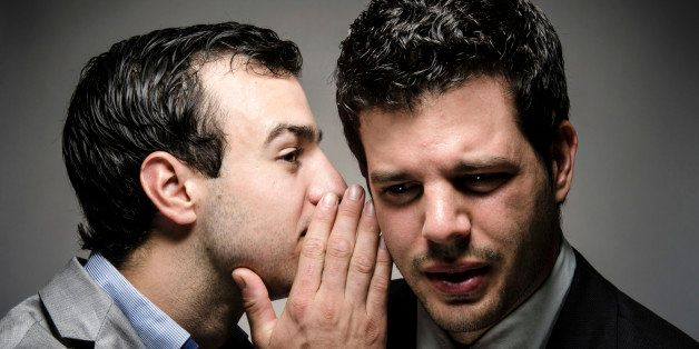 image of a young professional whispering to another