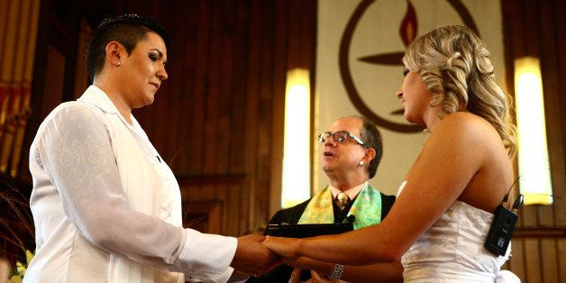 AUCKLAND, NEW ZEALAND - AUGUST 19:  Natasha Vitali (L) and Melissa Ray (R) exchange vows with marriage celebrant Rev Matt Tit