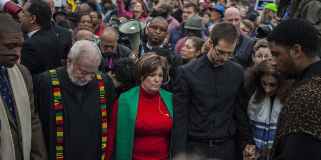 FERGUSON, MO - OCTOBER 13:  Clergy members lead hundreds of protestors march from Wellspring Church to the Ferguson police st