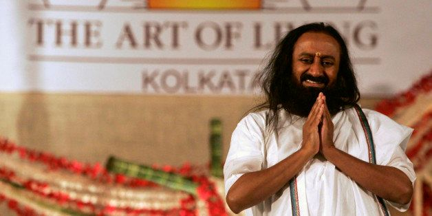 Indian spiritual guru and founder of The Art of Living Foundation Sri Sri Ravi Shankar greets followers as he arrives at a me