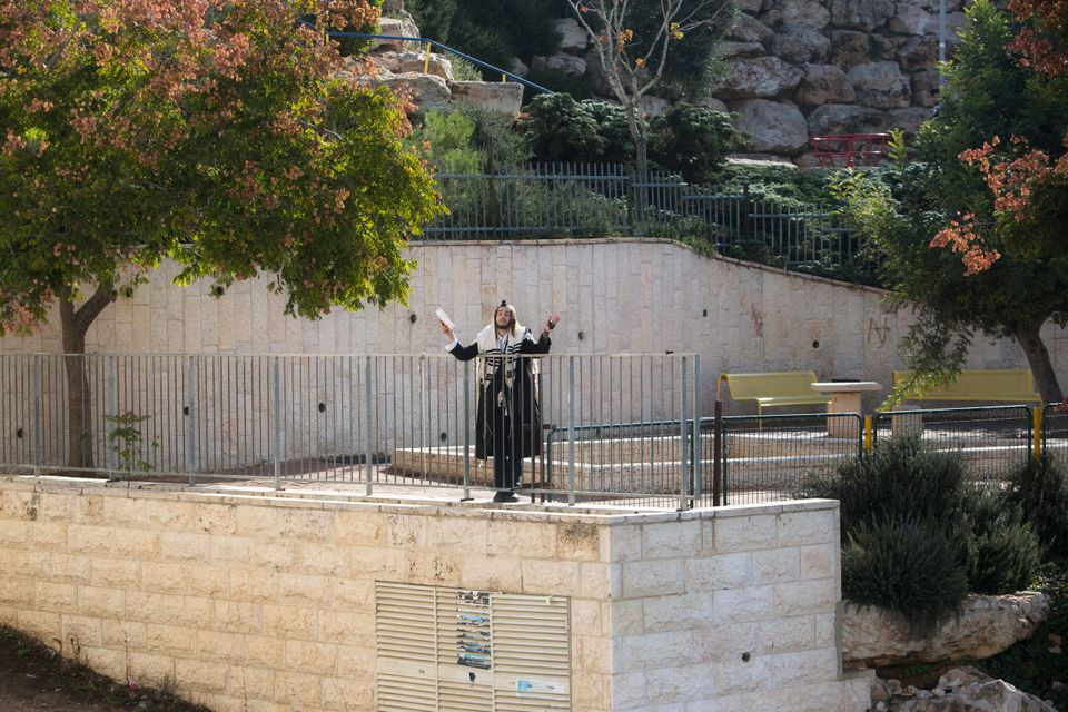 An ultra-Orthodox Jewish man prays at the scene of a shooting attack in a Synagogue in Jerusalem, Tuesday, Nov. 18, 2014. (AP