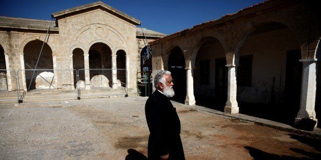A Greek Cypriot Orthodox priest monitors restoration work being done at the Apostolos Andreas Monastery in North Cyprus at Ri