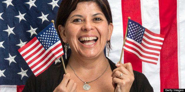 Happy hispanic  woman posing waving US flags with a US flag in the background