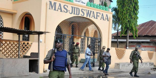 In this photo taken Wednesday, Nov. 19, 2014, armed police walk out of the Masjid Swafaa mosque after raiding it, in Mombasa,