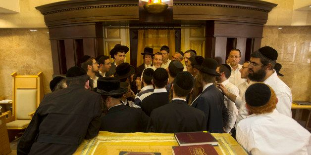 Ultra-Orthodox Jewish men gather around Yosef Posternac, center as he tells his account a day after a shooting attack at the