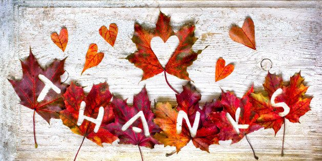 """Thanksgiving day concept/Autumn thanksgiving day background with red and yellow leaves with word """"Thanks"""" /Autumn leaves over wooden background"""