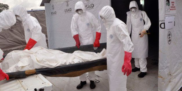 Health workers wearing Ebola protective gear remove the body of a man that they suspect died from the Ebola virus, at a USAID