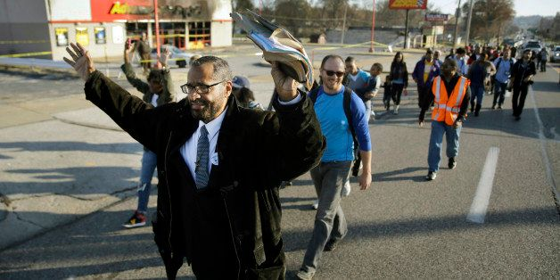 A large group walks past a burned-out business Saturday, Nov. 29, 2014, in Ferguson, Mo., early in a 120-mile march to the go