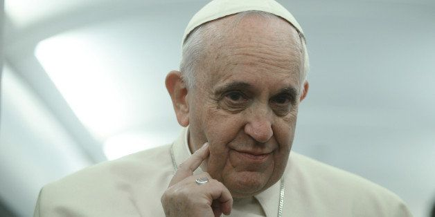 Pope Francis touches his face during a press conference aboard the flight towards Rome, Sunday, Nov. 30, 2014. Francis kicked