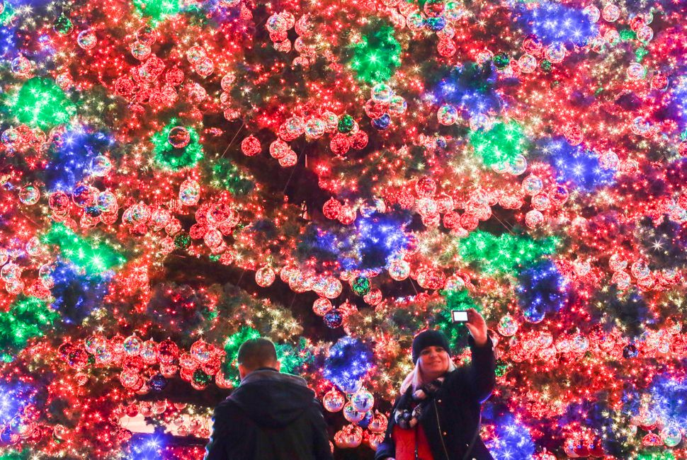 A woman takes a selfie in front of a colorful illuminated Christmas tree at Potsdamer Platz in Berlin, Germany, Tuesday, Nov.
