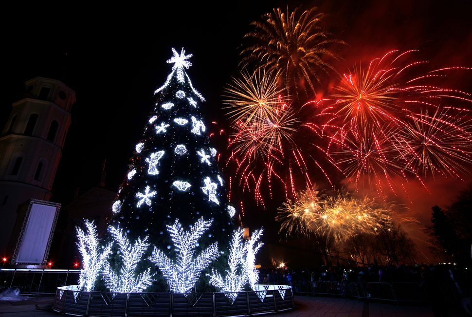 Fireworks light up the sky above a Christmas tree during a lighting ceremony at Cathedral  square in Vilnius, Lithuania, Satu