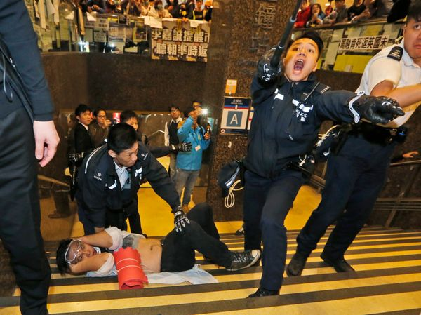 A protester lies on the stairway as police try to remove him and others from a tube station near government headquarters in H