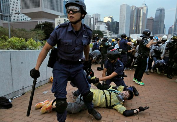 A protester is arrested by police officers outside government headquarters in Hong Kong