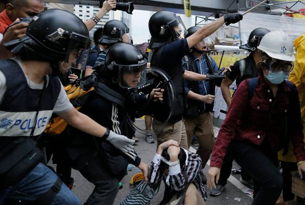 Protesters are dispersed by police officers outside government headquarters in Hong Kong