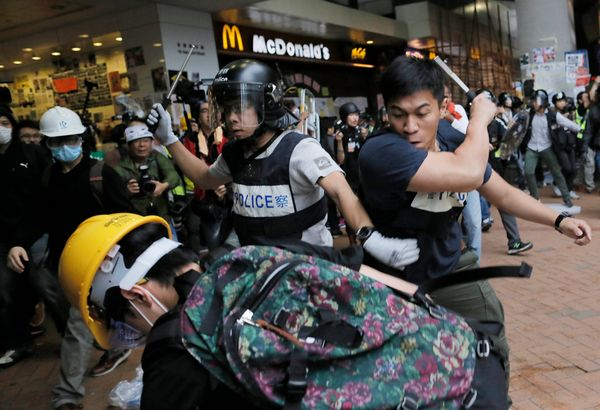Police officers beat up protesters as they try to disperse them outside government headquarters in Hong Kong