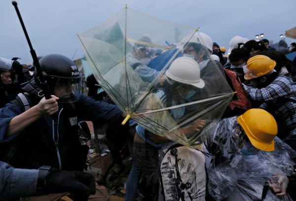 Police officers disperse protesters outside government headquarters in Hong Kong